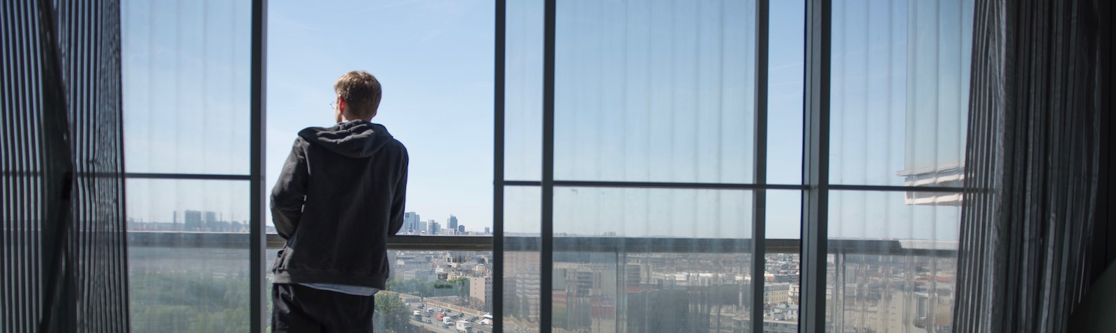 Man looking out of window in daylit building