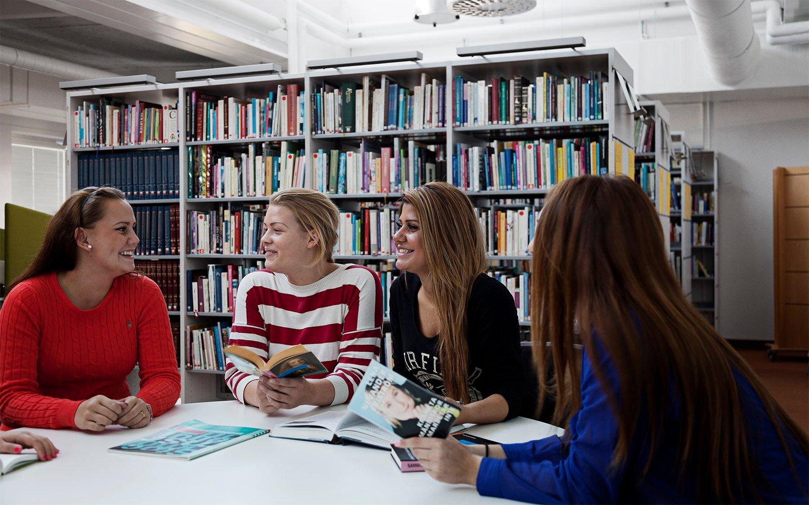 Studenter i Sågbäcksgymnasiets bibliotek, belysta av naturligt ljus