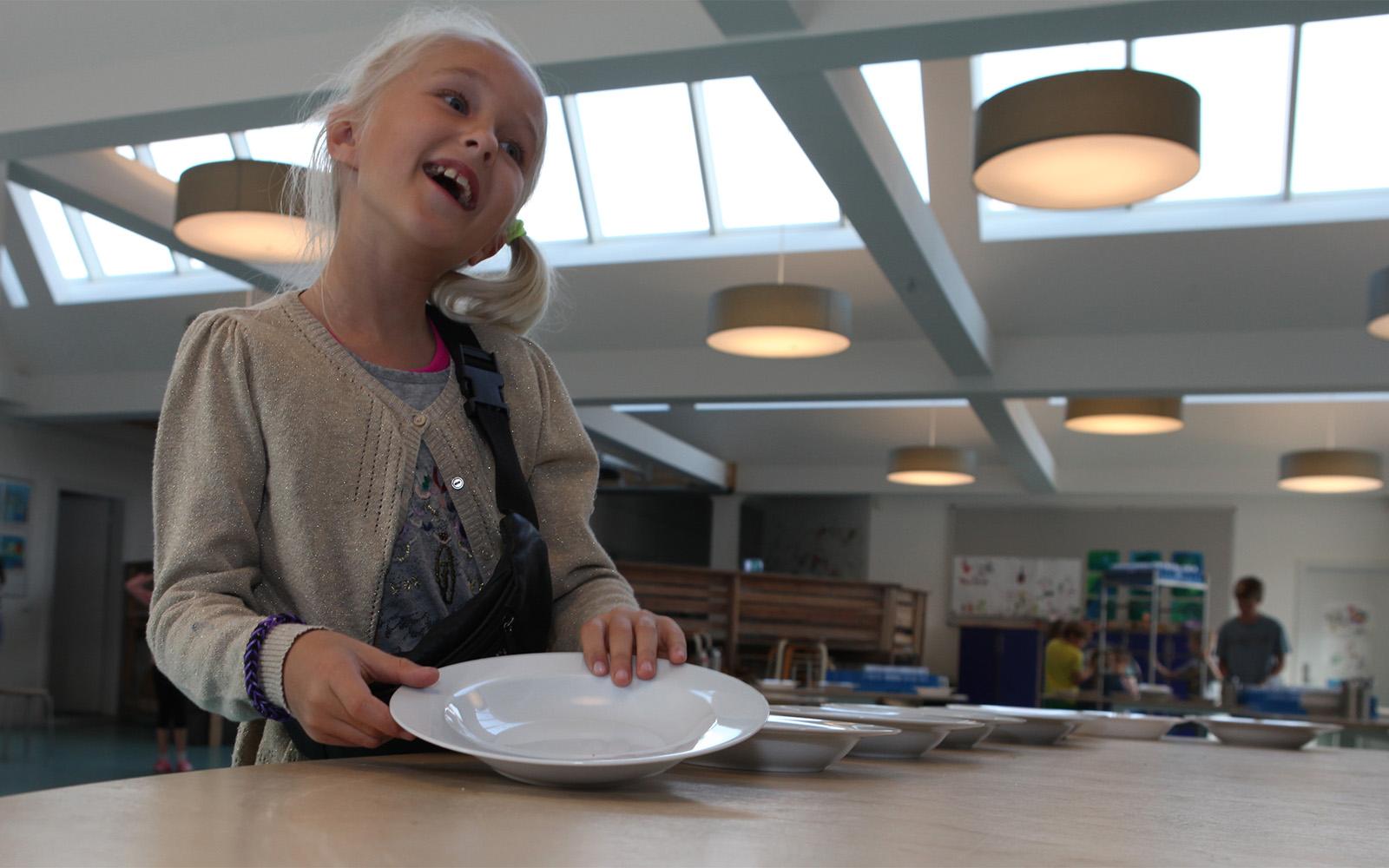 Ung student i cafeteria upplyst med naturligt ljus och konstgjord belysning