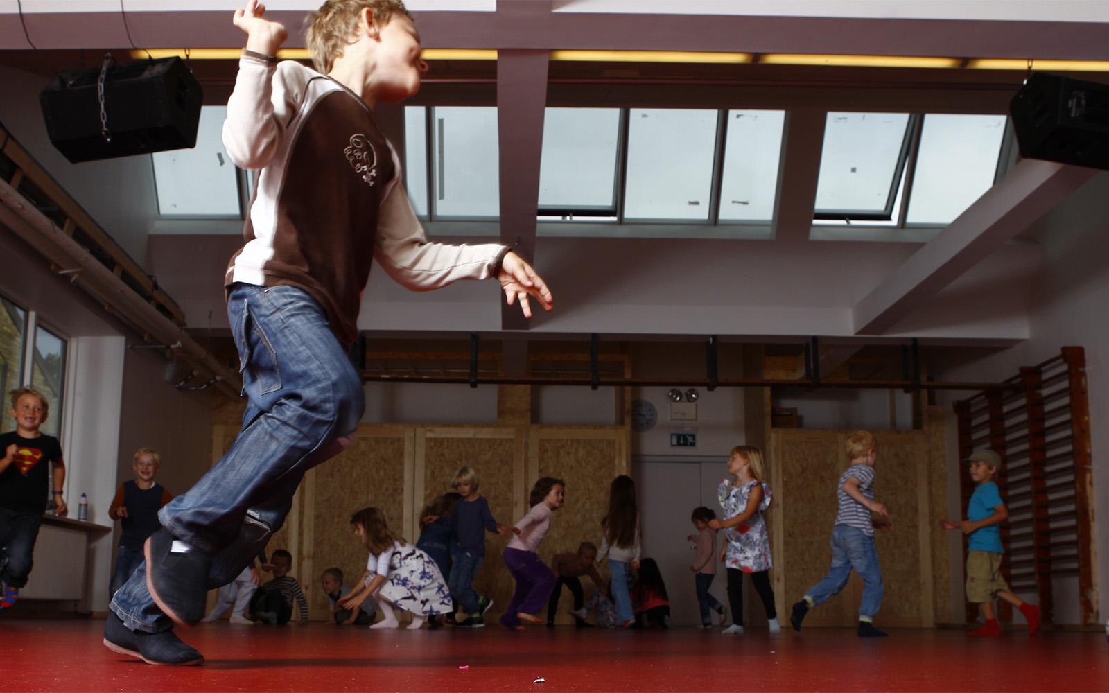 Små barn leker i skolans gymnastiksal med takfönster och takventilation