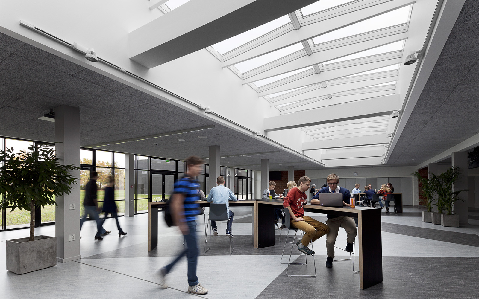 Lively school hall illuminated with natural light through VELUX skylights